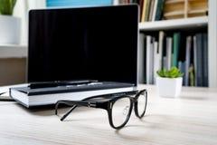 Stängd anteckningsbok på en bärbar dator, exponeringsglas och en grön blomma royaltyfria foton