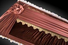 Stängd brun kista som täckas med den eleganta torkduken på grå bakgrund kistanärbild med guld- blommor Arkivbild
