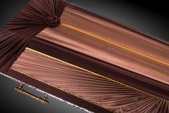 Stängd brun kista som täckas med den eleganta torkduken som isoleras på grå bakgrund kistanärbild Arkivbild