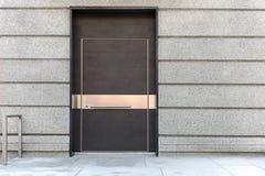 Stängd brun metalldörr på grå byggnadsfasad Royaltyfri Foto