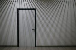 Stängd dörr med korsningen linjer av ljus och skuggor som faller på Royaltyfri Bild