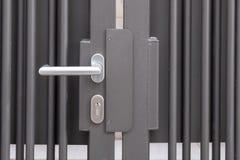 Stängd järnport med dörrhandtaget arkivbild