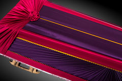 Stängd röd och lilakista som täckas med den eleganta torkduken på grå bakgrund kistanärbild Arkivfoto