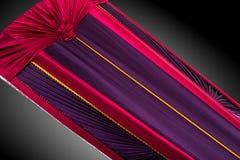 Stängd röd och lilakista som täckas med den eleganta torkduken som isoleras på grå bakgrund kistanärbild Arkivfoton