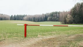 Stängd röd och vit barriär på skogingången arkivbild