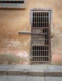 Stängd rostad dörr för cell för järnstänger och riden ut grungestenvägg i stängt övergett fängelse royaltyfria foton