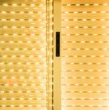 Stängd rullgardin som ljus skriver in i slitsarna Arkivbild