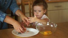 Stängd stående av en flicka i köket Dottern själv bryter äggen in i en bunke Mamman torkar hennes händer med a arkivfilmer