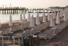 Stängd vit paraplyer, solstolar och pir på en tom strand Royaltyfri Bild