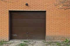 Stängda bruna dörrar på tegelstenväggen av garaget Royaltyfri Bild