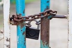 Stängda portar med hänglås- och järnkedjan metalliska texturer, sjaskig turkosmålarfärgyttersida Moget frö av granatäpplet Säkerh fotografering för bildbyråer