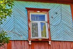 Stängda slutare av det lantliga fönstret på den lantliga trähusväggen Arkivfoton