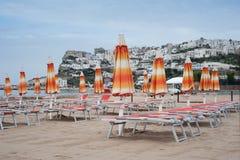 Stängda strandparaplyer och solstolar på en tom strand Fotografering för Bildbyråer
