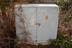 Stängde sig den utomhus- asken för grå elektrisk hög spänning med rostat låser lokaliserat på det övergav industriella komplexet  royaltyfria bilder