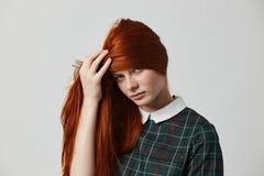 Stänger den långhåriga flickan för den härliga rödhåriga mannen i en grön rutig klänning hennes framsida med hennes hår på den vi arkivfoto