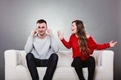 Stänger den skrikiga mannen för den ilskna raserikvinnan hans öron arkivbilder