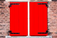 Stänger med fönsterluckor det brun tegelsten stängda svart förfalskade röda fönstret för järn den gråa stenväggen arkivfoto