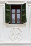 Stänger med fönsterluckor det gröna träfönstret för klassikern på ett byhus Royaltyfria Bilder