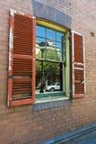 Stänger med fönsterluckor gammal skadad gatareflexion arkivfoton