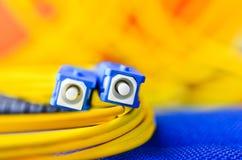Stänger sig optiska kontaktdon för fiber upp på en färgglad bakgrund Arkivfoto