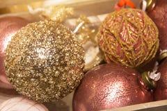 Stänger sig röda guld- skinande bollgarneringar för jul upp royaltyfri fotografi