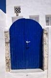 Stängt mörker - blå dörr i ett grekiskt hus Royaltyfri Fotografi