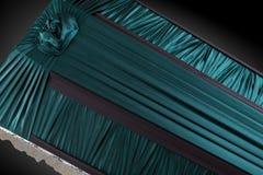 Stängt mörker - grön kista som täckas med den eleganta torkduken på grå bakgrund kistanärbild Royaltyfria Foton