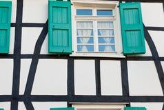 Stängt med fönsterluckor fönster i ett tyskt timmerramhus Royaltyfria Foton