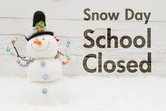 Stängt meddelande för skola med en snögubbe arkivfoto