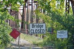 Stängt tecken för bro framme av den förfallna bron med overgrowth av träd och buskar royaltyfri bild