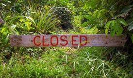 Stängt tecken på träbräde i solig sommarträdgård Träbräde med den stängda inskriften Arkivbild