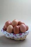Stängt upp ägg i härlig korg på grå bakgrund royaltyfri bild