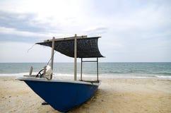 Stängt upp fiskarefartyget strandade på den sandiga stranden och den molniga himlen Arkivbild