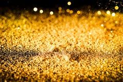 Stänket blänker guldstoft på en svart bakgrund royaltyfri fotografi