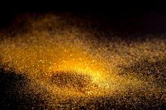 Stänket blänker guldstoft på en svart bakgrund royaltyfri bild