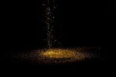Stänkguldstoft på en svart bakgrund Arkivfoto