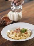Stänkkryddor på spagetti Carbonara Fotografering för Bildbyråer