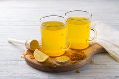 Stärkande drink för energi med gurkmeja, ingefäran, citronen och honung arkivbilder