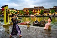 St? fr?nsett massturism p? andra sidan av kanalen i den turist- destinationen Hoi An, vietnamesiska kvinnor i Hoi An, Vietnam royaltyfria foton