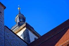 Stå högt med en tornspira, stenväggar, taket som täckas med röda tegelplattor Arkivbilder