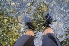 Stå i den kristallklara floden med kortslutningar och fotvandra kängor på arkivfoto