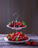 Stå med jordgubbar och choklader på en trätabell Royaltyfria Bilder