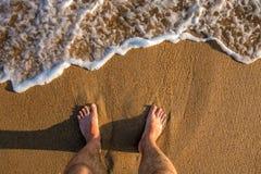 Stå på shorelinen, medan spuming havsvatten svaller in mot brun sand på solnedgången arkivfoton