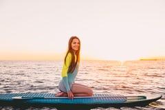 Stå upp skovellogi på havet med varma solnedgångfärger Ung flicka som kopplar av på havet Royaltyfri Bild