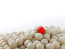 Stå ut den röda bollen på kullen av vita bollar Arkivbilder