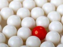 Stå ut den röda bollen som omges av vita bollar Arkivfoton
