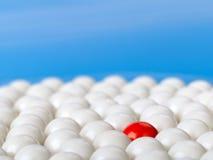 Stå ut den röda bollen som omges av vita bollar på blå bakgrund Arkivfoton