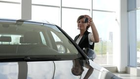 Ståendeägarebilen, kvinna ler och visar i handtangent till nytt lager videofilmer