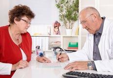 Stående: äldre doktor med erfarenhet som talar med den höga kvinnan Royaltyfria Bilder