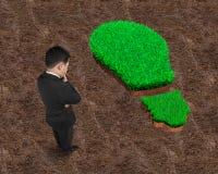 Stående affärsman som grubblar över grönt gräs av den ljusa kulan Fotografering för Bildbyråer